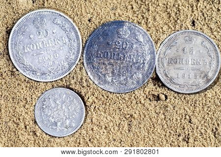 Four Coins On Sand, Old Silver Coins Of Russia Of The 18th Century, Coins Of The Russian Kopeks Take