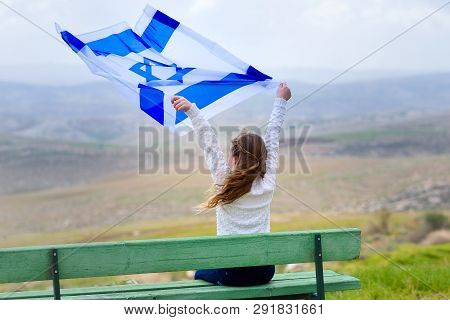 Beautiful Young Jewish Girl Sitting Holding Israel Flag In The Wind And Enjoying Great View Landscap