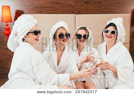 Bachelorette Party Fun. Cheerful Young Females In Sunglasses, Bathrobes And Towel Turbans Clinking C