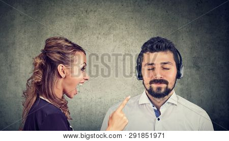 Angry Woman Yelling At A Calm Husband Listening To Music With Headphones
