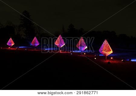 Five Decorative Fixtures Illuminated By Colorful Floodlights In Park During Holidays