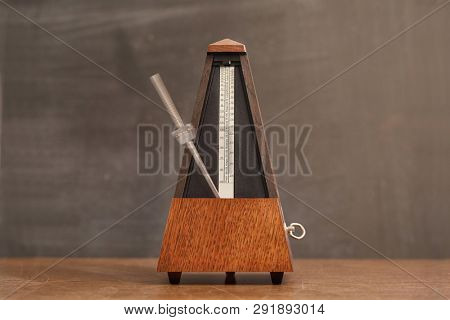 Classic metronome on a table, motion blurred hand