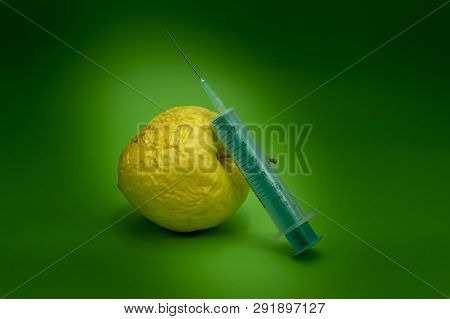 Old withered fresh apple with hypodermic needle, concept of healthcare, plastic surgery, treatment, research and medicine over a green background poster