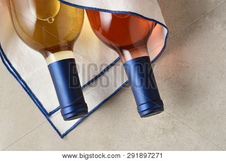 A bottle of White Zinfandel and Sauvignon Blanc wine wrapped in a tea towel on a gray tile surface.