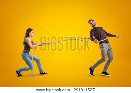 Side View Of Young Woman Lassooing Young Man On Yellow Background.