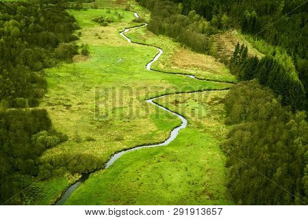 Curvy River Running Through A Green Area With Fields And Forest Seen From Above