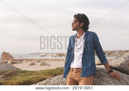 Front view of thoughtful Caucasian man standing and leaning at beach on a sunny day. He wears sunglasses