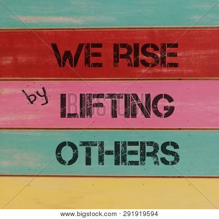 We rise by lifting other, stencil print on colorful wooden panel