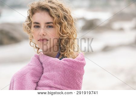 Front view of caucasian woman standing on beach while looking at camera