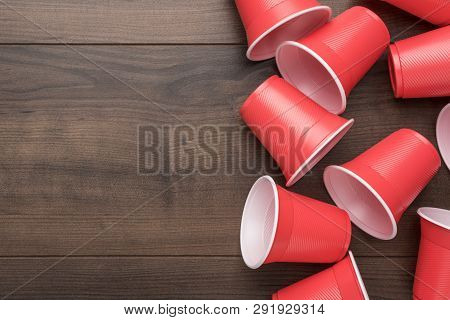 Disposable Plastic Cups On The Wooden Background. Top View Of Used Plastic Cups. Red Plastic Cups On