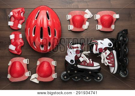 Roller Skates And Body Parts Protection. Roller Skates On Brown Table. Top View Of Roller Skates, He