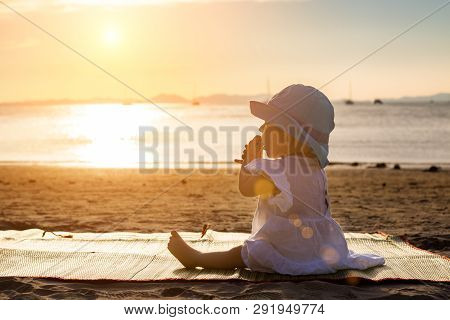 The Baby Is Teething. Everything Gnaws, Chewing. Infant Girl Sitting On The Tropical Sand Beach And