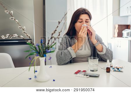 Spring Allergy. Young Woman Sneezing Because Of Flowers Surrounded With Pills On Kitchen. Seasonal A