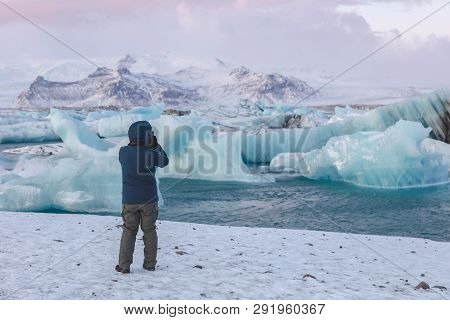 Photographer Shooting Glacier Ice In Jökulsárlón Lagoon, Iceland On A Cold Winters Day.