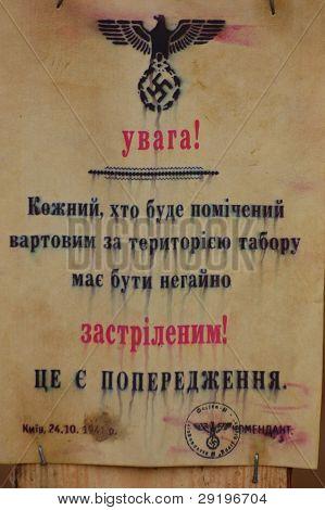 KIEV, UKRAINE -NOV 6: Nazi poster replica in Ukrainian(Translation - Restricted area.No trespass.Civilian will executed) during historical reenactment of WWII, November 6, 2011 in Kiev, Ukraine