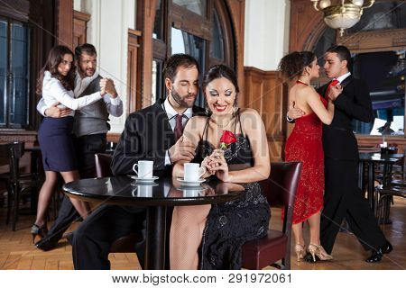 Happy Couple With Rose Smiling While Enjoying Tango Performance