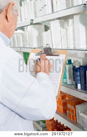 Pharmacist Writing On Clipboard While Counting Stock In Pharmacy