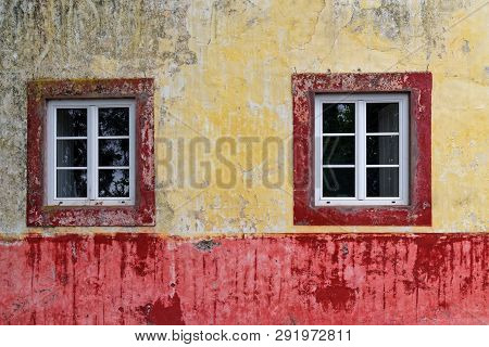 Two Windows On An Old And Dirty Wall Of Colorful House Facade
