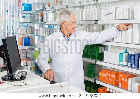 Chemist Removing Bottle From Shelf While Working On Computer
