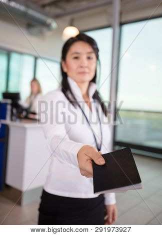 Female Staff Giving Passport At Airport Terminal