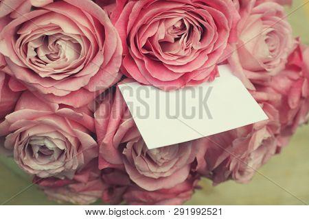 Blank greeting card in a bouquet of roses