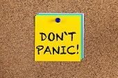 Notes with words Don`t panic! on corkboard (bulletin board). poster