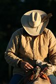 A cowboy is getting ready for a morning of roping cattle on his ranch in Colorado. He is sitting on his horse and is basked in the first rays of sunlight just after dawn. poster