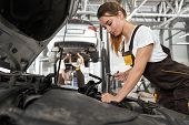 Beautiful girl with ponytail, wearing in coveralls and white t shirt working in autoservice as mechanic. Pretty, handsome young woman fixing under car hood, using tool, equipment. poster