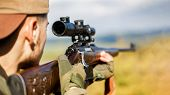 Hunter is aiming. Shooter sighting in the target. Hunter man. Hunting period. Male with a gun. Close up. Hunter with hunting gun and hunting form to hunt. The man is on the hunt. Hunt hunting rifle. poster