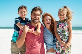 Portrait of happy family looking at camera at beach. Cheerful mother and father with cute daughter and son at sea during weekend. Smiling family with two children enjoying vacation at beach.