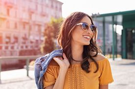 Happy latin woman walking on the street on a bright sunny day. Cheerful stylish girl with sunglasses enjoying the spring. Young woman wearing shades while looking away in the afternoon.