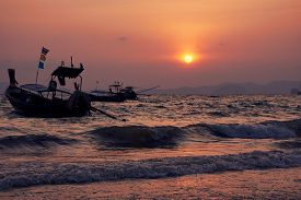 Boat in the wavy sea and sunset at Khlong Muang Beach, Krabi, Thailand.