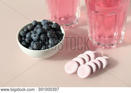 Vitamin C blueberry effervescent tablets, two cups of prepared blueberry flavored drink, and fresh blueberries on a pink table