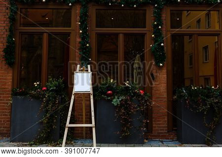 Traditional Christmas Decorations Outside The Cafe. Christmas Wreaths On The Windows And Decorated L