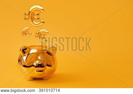 Golden Piggy Bank On Yellow Background With Gold Euro Sign Balloons. Golden Currency Symbol Made Of