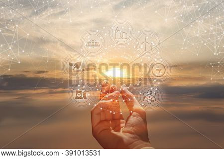 The Hand Shows Alternative Energy Sources On The Background Of A Sunny Sunset.