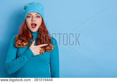 Astonished Caucasian Woman Indicates Away, Shows Blank Space For Your Advertisement, Red Haired With