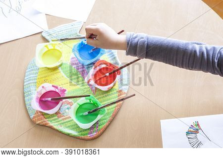 Child Hand Soaking Artist Brush On Washable Tempera Paint. Yogurt Cups Reused As Paint Containers