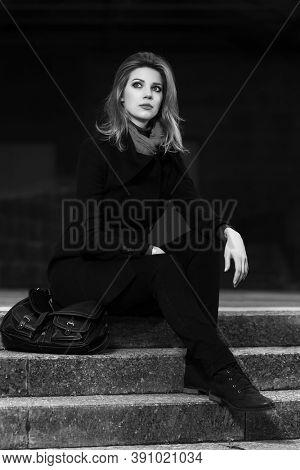 Fashion blonde business woman sitting on steps Stylish female model in classic black coat