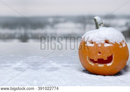 A Jack-o'-lantern Carved Pumpkin During A Snow Fall During The Fall. Concept: Cold Halloween. Snow F