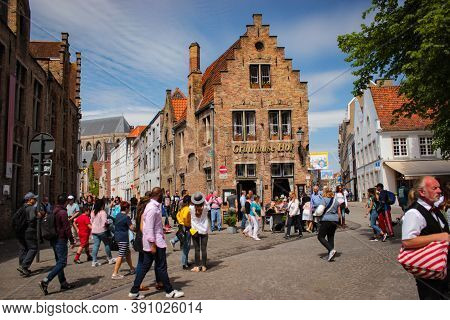 Bruges, Belgium - May 12, 2018: Tourists And Locals Walk On A Sunny Day