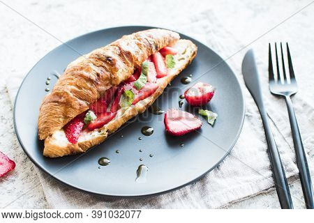 Croissant With Strawberries, Soft Cheese, Mint And Honey On Black Plate On Grey Background.