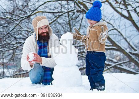 Happy Father And Son Making Snowman In The Snow. Handmade Funny Snow Man. Winter Background With Sno