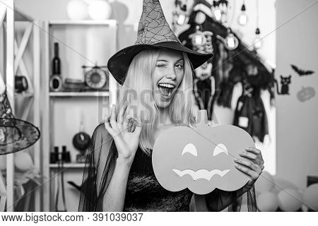 Beautiful Young Surprised Woman In Witches Hat And Costume Holding Pumpkin. Surprised Woman In Witch