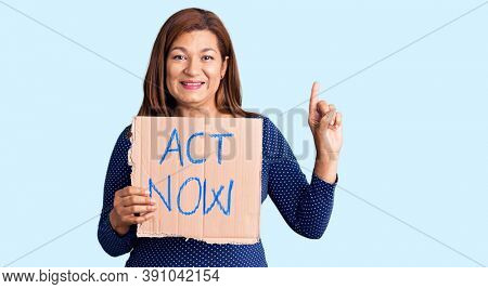 Middle age latin woman holding act now banner surprised with an idea or question pointing finger with happy face, number one