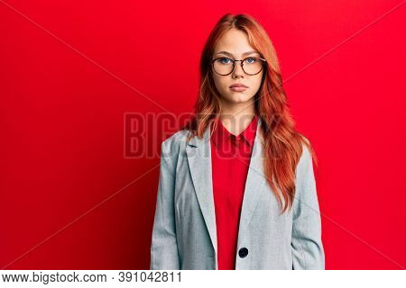 Young redhead woman wearing business jacket and glasses with serious expression on face. simple and natural looking at the camera.