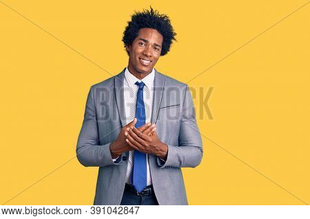 Handsome african american man with afro hair wearing business jacket with hands together and crossed fingers smiling relaxed and cheerful. success and optimistic