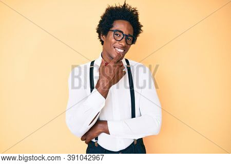 Handsome african american man with afro hair wearing hipster elegant look looking confident at the camera with smile with crossed arms and hand raised on chin. thinking positive.