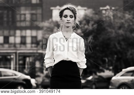 Young business woman on city street Stylish fashion model in white shirt and black pencil skirt