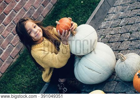 Funny Child Girl In Orange Pullover For Halloween With Pumpkin And On A Dark Brick Background.